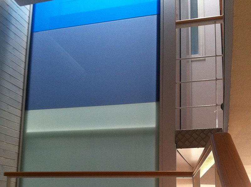 vidrios laminados en diferentes tonos azules que forman la estructura de un ascensor